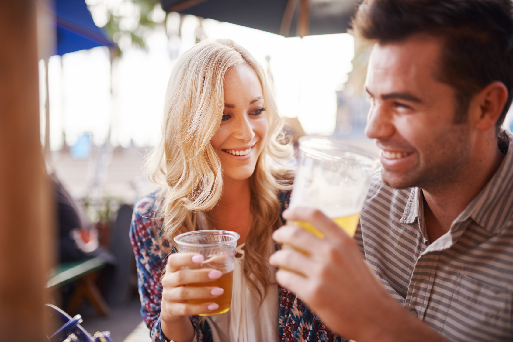happy couple drinking beer together at outdoor pub or bar